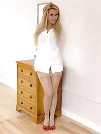 Hot blonde in her bedroom wearing red high heels and nylon..