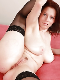 Busty housewife Carol spreads her black stocking clad legs..