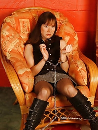 Kinky brunette is left chained up on sofa in sexy leather..